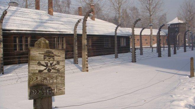 """Os avisos de perigo serviam não apenas pelo fato da cerca ser eletrificada, mas também pelo fato de que os prisioneiros que andassem na """"zona morta"""" (não vista na foto devido à neve) seriam fuzilados pelos guardas presentes nas torres"""