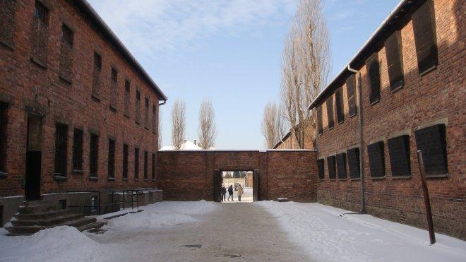 Notem que as janelas do bloco 10, à direita, eram tampadas. O objetivo era evitar que os prisioneiros deste bloco vissem o que ali acontecia. As salas do bloco 11, à esquerda, eram ocupadas pelos nazistas; daí as janelas não serem cobertas. Notem, à direita, um mastro, no qual alguns prisioneiros eram enforcados (o muro de fuzilamento da foto anterior está atrás de mim)