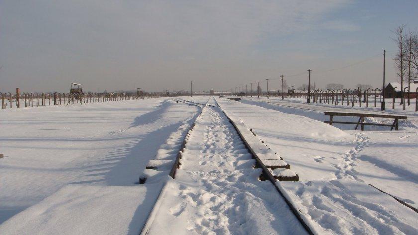 Linha férrea dentro de Birkenau, com a entrada do campo ao fundo